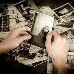 Man hält ein Foto vor einem Tisch voller Bilder